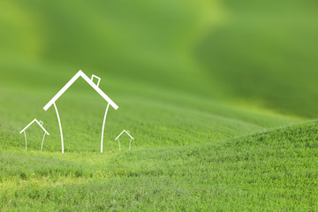 Eco friendly house icons on sunny blurred green meadow landscape background. Selective focus used.