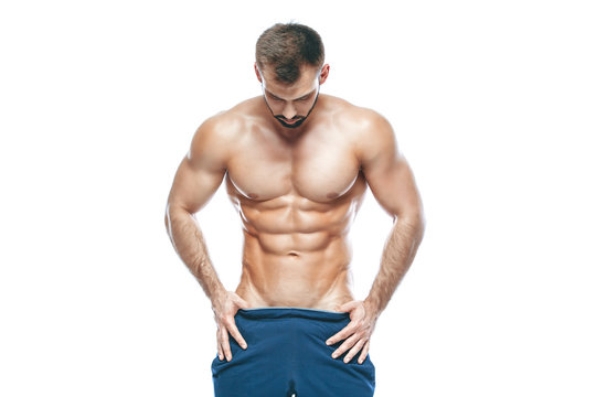 bodybuilder posing. Beautiful sporty guy male power. Fitness muscled in blue shorts. on isolated white background. Man with muscular torso. Strong Athletic Man Fitness Model Torso showing six pack abs