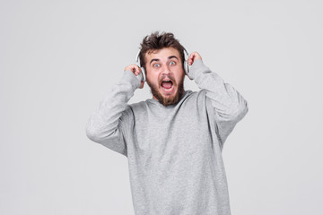 Shock. A young man with a beard in casual clothes with horror on his face listens to loud music in wireless headphones. Gray background with space for text