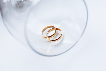 Wedding golden rings in transparent glass. Symbol of love and marriage. Creative picture with glass glittering in the sunlight.