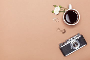 Top view of a cup of coffee, a branch of a white rose, gold rings and a vintage camera with space for text. Woman background. flat lay