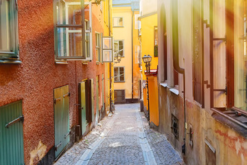 The narrow cobblestone street with a bicycle and medieval houses of Gamla Stan historic old center of Stockholm at summer sunny day.