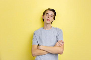 Calm handsome young thin dark-haired guy with blue eyes wearing gray t-shirt standing against yellow background with crossed hands