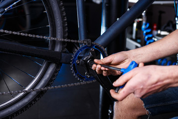 Close-up of man's hands bicycle mechanics in the shop uses instment to adjust and repair the bicycle crank assembly, bicycle chainrings
