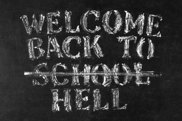 "Back to school background. ""WELCOME BACK TO school - HELL"" white chalk text on school backboard."