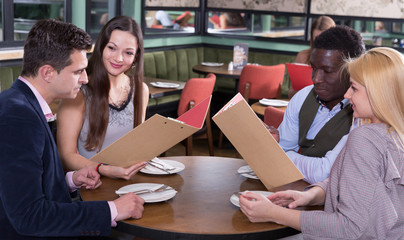 Friends choosing dishes from restaurant menu