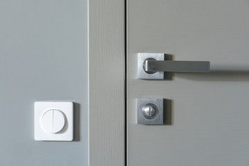 A metal handle and a lock on the gray interior door and a white switch on the gray wall. Element of apartment design. Wall mural