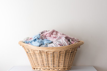 Closeup of wicker basket with blue and pink washing against white wall.