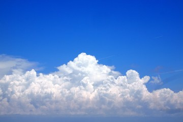 Huge white cumulus clouds computing over blue summer sky with contrails