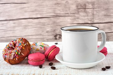 Coffee, donuts and macaroons over a wood background. Side view table scene.