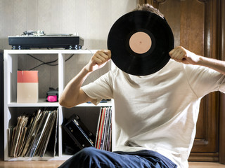 young man sitting in cozy living room holding the vinyl record disk near the records rack on the floor