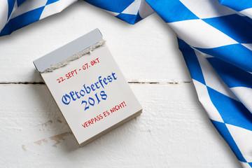 """Tischtuch mit bayrischem Rautenmuster auf Holzuntergrund und Abreißkalender mit Aufschrift """"Oktoberfest 2018"""""""