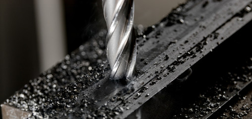 Bridgeport CNC end mill finishing a stack of steel plate with metal filings chips around