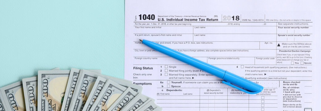 1040 tax form lies near hundred dollar bills and blue pen on a light blue background. US Individual income tax return