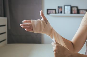 Woman using elastic bandage with hand,Female putting bandage on his injured hands