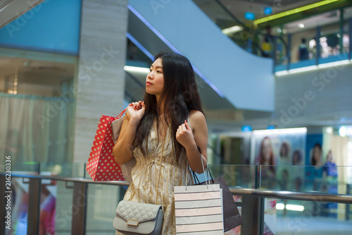 6f4d4480463 lifestyle indoors portrait of young happy and beautiful Asian Korean woman  carrying shopping bags in mall buying cheerful walking around fashion store