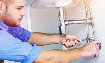 Handsome Professional plumber fixing pipes