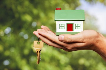 Businessman Holding House Model and Keys
