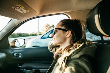 Portrait of a young passenger girl inside the car. Daily trips on transport or tourism, road travel or adventure. Wall mural