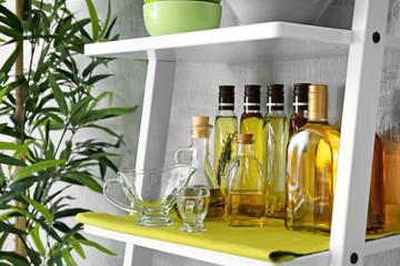 Gravy boats and bottles on white shelf
