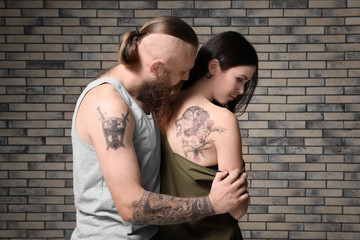 Attractive young couple with tattoos on brick wall background