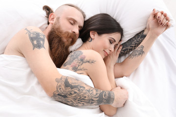 Attractive young couple with tattoos in bed