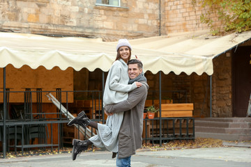 Beautiful couple in warm clothes on city street