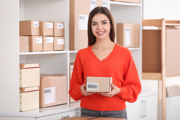Young woman preparing parcel for shipment to client in home office