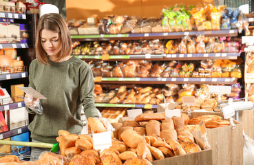Beautiful woman with product list choosing fresh bakery in supermarket