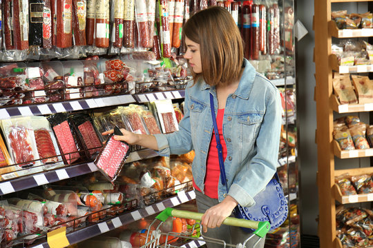 Beautiful woman choosing sausage products in supermarket