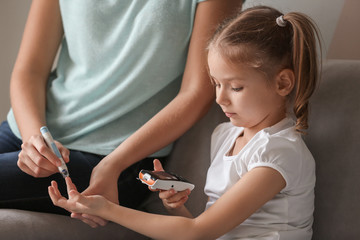 Woman and her diabetic daughter with lancet pen and digital glucometer taking blood sample at home