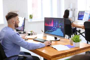 Young man working with stock data in office. Finance trading