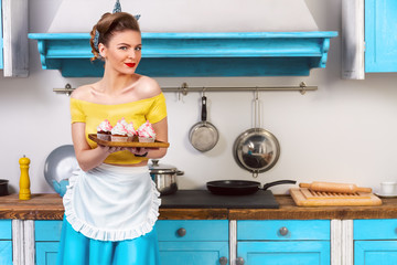 Retro / pin up girl / housewife wearing colorful top, skirt and white apron holding tray with sweet cupcakes standing in the kitchen with blue cabinets and utensils.
