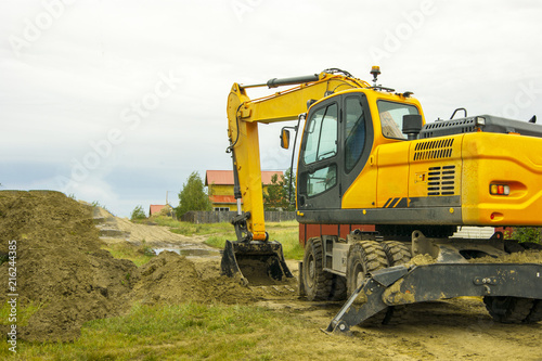 Yellow excavator begins to dig a trench in the ground
