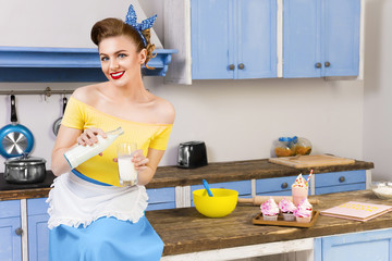 Colorful retro / pin up girl woman female / housewife wearing colorful top, skirt and white apron sitting in the kitchen pouring some milk from bottle into glass. Cupcakes and milkshake in the table