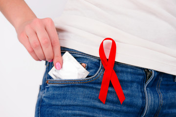 Safe sex healthcare concept. Young girl woman female adult wearing jeans with pinned red ribbon as a symbol of hiv /aids putting condom into pocket