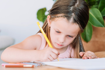 child painting hobby. artful kids leisure. focused little girl drawing and expressing her imagination on paper.