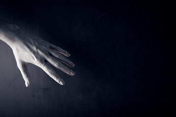 White painted hand on a black background. Abstract. Copy space