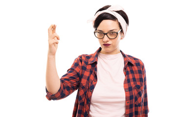 Young pretty pin-up girl wearing glasses showing cross finger gesture.
