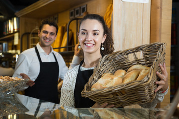 Smily italian woman and good-looking man selling delicious pastry