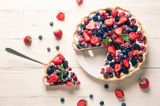 Delicious berry pie on white wooden table