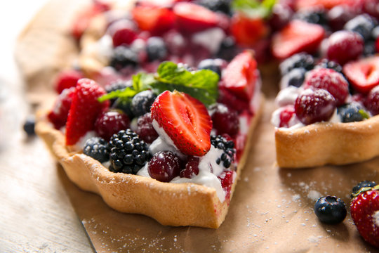 Delicious pie with ripe berries on table, closeup