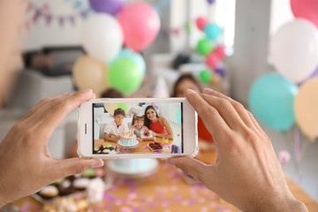 Young man taking photo of family while celebrating daughter's birthday at home