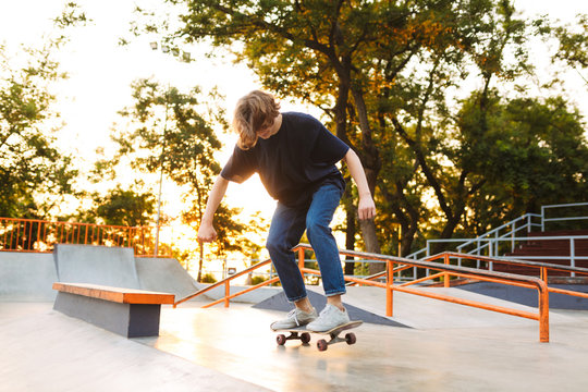 Young cool skater in black T-shirt and jeans riding on skateskateboard at skate park