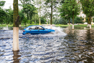 The car driving on a flooded road during a flood caused by heavy rain