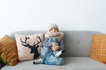 The child in a knitted cap and with a warm scarf sitting on a sofa