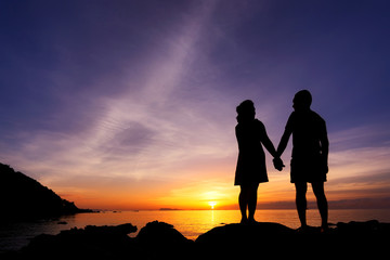 Silhouette of couple hold one's hands on the beach