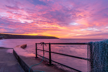 Sunrise at Filey fishing jetty looking towards Filey Brigg, Yorkshire, UK