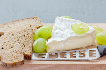 Cheese, grapes, bread and knife lie on a wooden board
