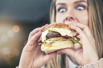 Wide-eyed girl looks down at enormous burger